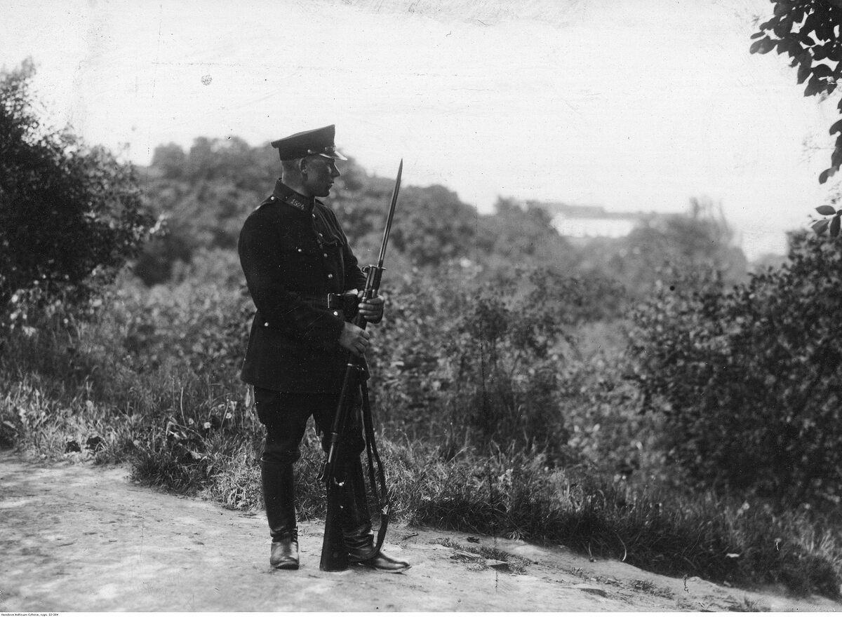 Policjant (trzyma karabin Enfield P14) na czatach podczas obławy w okolicy podmiejskiej (1926 r.)