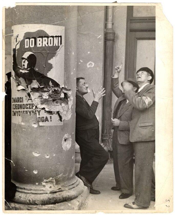 """Przed Teatrem Wielkim. Członkowie ochotniczej policji obserwują niemiecki nalot. Obok nich poszarpany plakat z napisem: """"Do broni. Zwarci i zjednoczeni zwyciężymy wroga!"""""""