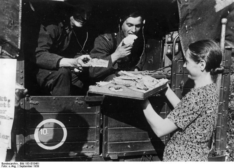 """Kobieta, która ma być etnicznie pochodzenia niemieckiego, częstuje żołnierzy Wehrmachtu kanapkami """"Wyzwolona ludność etnicznie niemiecka wita wszędzie nasze wojska w najbardziej przyjazny sposób i pomaga im, gdzie tylko może"""" – tak zdjęcie podpisała nazistowska propaganda"""