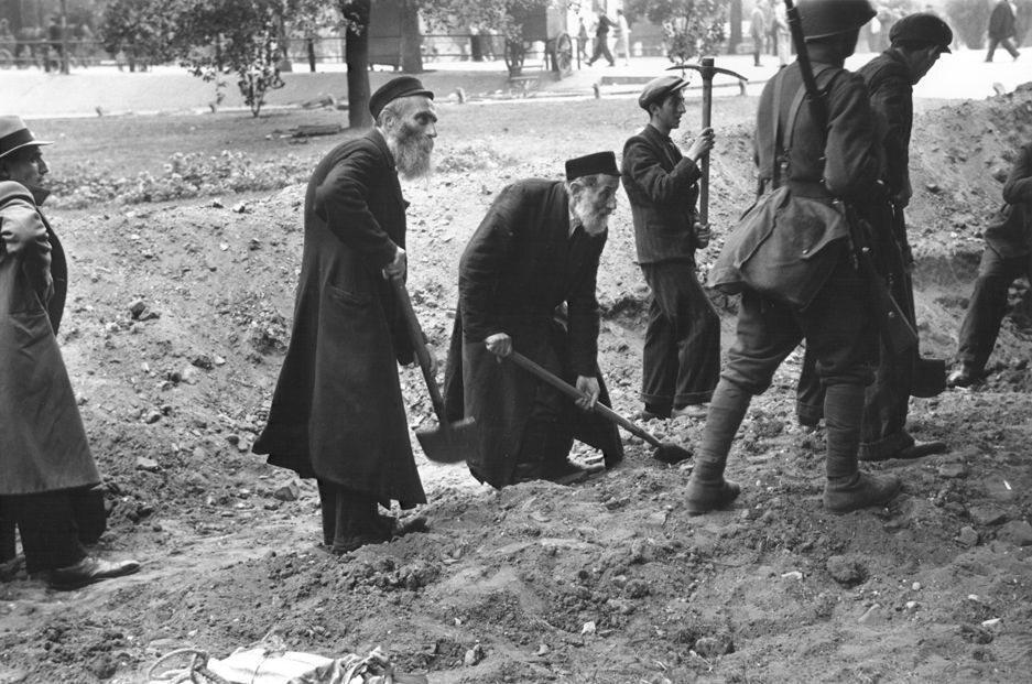 Starsi Żydzi ubrani w charakterystyczne okrycia (chałaty) biorą udział w kopaniu rowów przeciwpancernych, prace nadzoruje wojsko