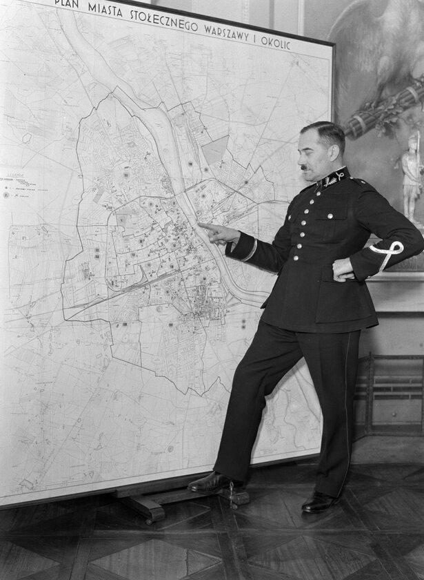 Oficer warszawskiej policji wskazuje na punkt na mapie miasta (1934 r.)