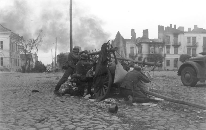 """Niemieccy żołnierze prawdopodobnie w czasie walki o Sochaczew """"Walki uliczne. Niemieccy żołnierze za osłoną z drewnianych wozów"""" – brzmi propagandowy podpis"""