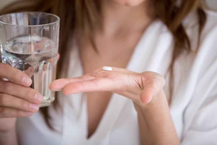 Kobieta trzymająca na dłoni tabletkę