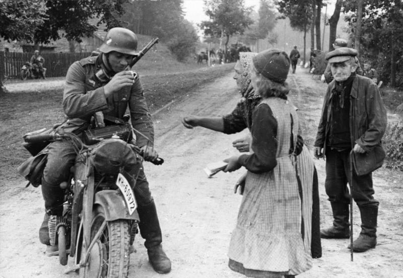 """Niemiecki żołnierz na motocyklu jest częstowany piciem przez starsze kobiety """"Volksdeutsche wręczyli swoim wyzwolicielom świeży napój"""" – głosi niemiecka propaganda"""