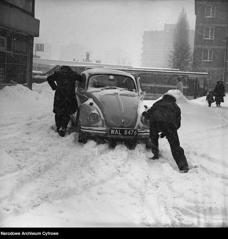 Zima Stulecia na Wierzbnie w Warszawie. Mężczyźni pchający samochód Volkswagen Garbus