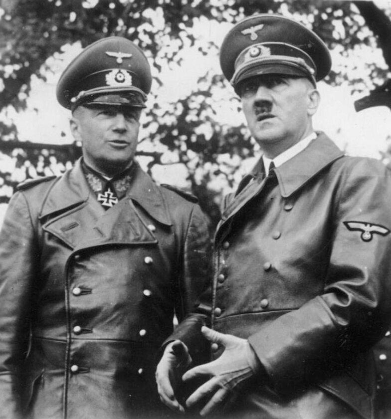 """Adolf Hitler i Walther von Brauchitsch w skórzanych płaszczach na paradzie w Warszawie """"Po raz kolejny nadszedł dzień, kiedy dzięki śmiałej decyzji Führera zerwano jeden z najtrudniejszych i najbardziej uciążliwych kajdan Wersalu, a Niemcy odzyskały swoją wolność."""" – głosi propagandowy podpis pod zdjęciem"""
