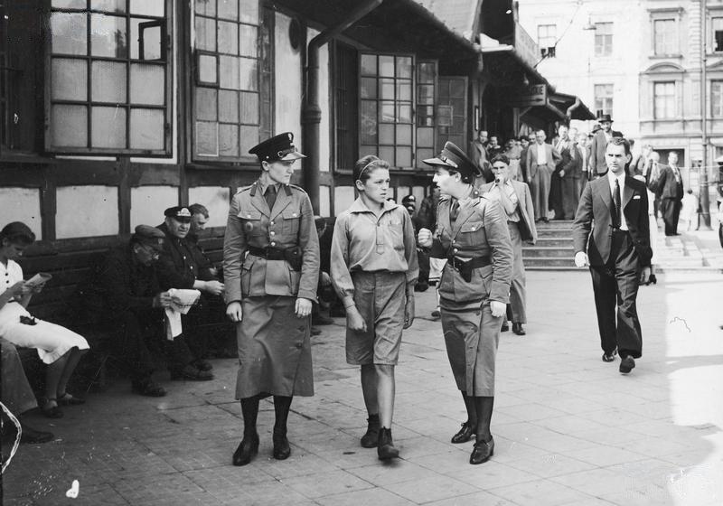Dwie funkcjonariuszki Policji Kobiecej eskortują zatrzymanego młodocianego do policyjnej izby zatrzymań. W tle budynek tzw. Dworca Głównego Tymczasowego przy ulicy Chmielnej (1939 r.)