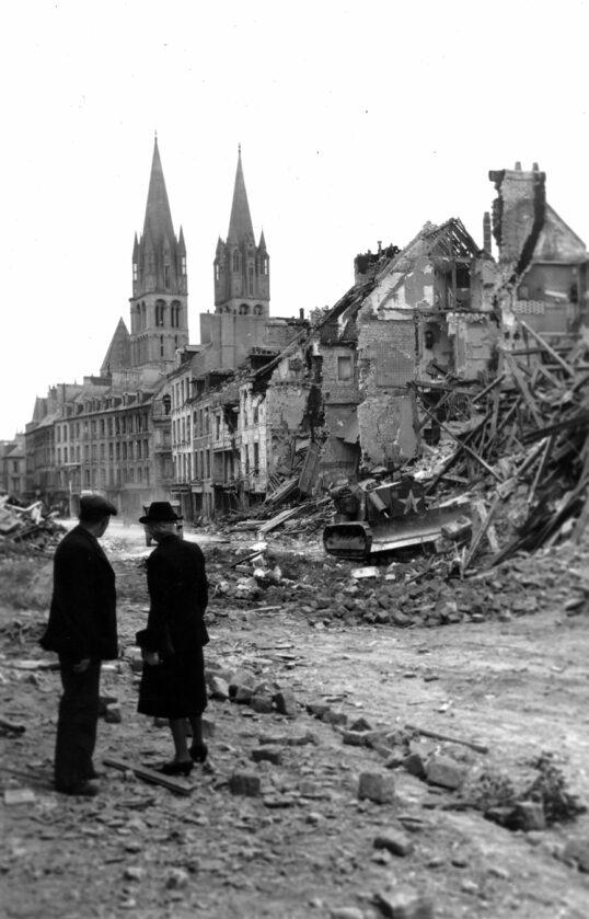 Para mieszkańców Caen obserwuje kanadyjski buldożer oczyszczający drogę. W tle widoczne Abbaye aux Hommes - Opactwo Męskie (10 lipca 1944).