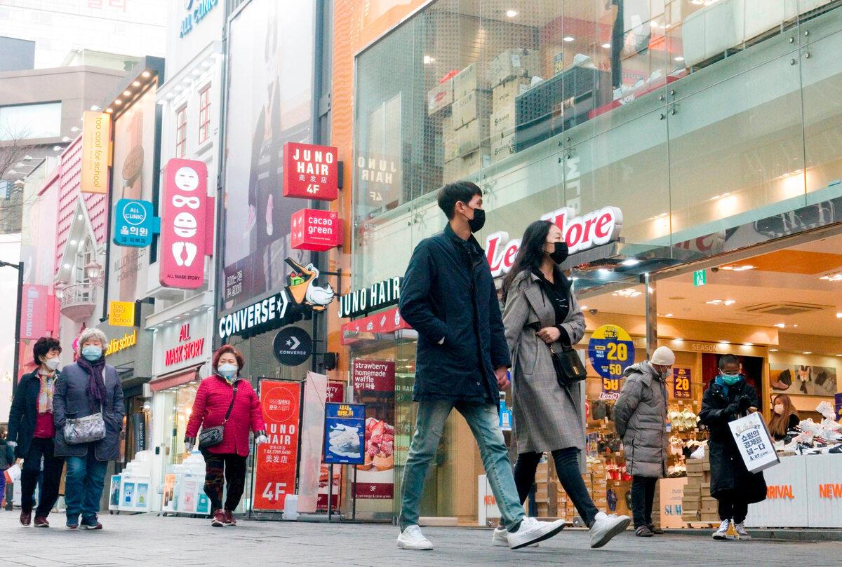 Przechodnie przed centrum handlowym w Seulu (13 marca)
