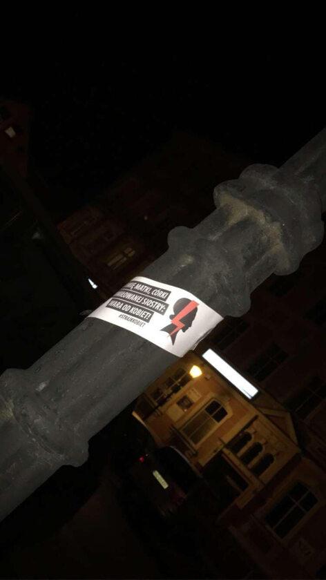 Wlepka na latarni koło kościoła