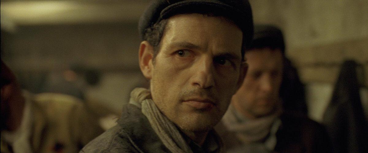 """#3. """"Syn Szawła"""", reż. László Nemes (Węgry 2015) Nagrodzony Oscarem """"Syn Szawła"""" to zaprzeczenie kina pojmowanego jako rodzaj rozrywki. W swej opowieści o więźniach obozu Auschwitz-Birkenau László Nemes zdobył się na pełny naturalizm, przez co seans jego filmu jest doświadczeniem wstrząsającym, ważnym i skrajnie trudnym. Dokładny obraz zagłady nie służy jednak szokowaniu czy kontrowersji. Ciasny kadr, w środku którego niemal zawsze znajduje się twarz Szawła – członka Sonderkommando, stawia apokaliptyczne widoki na drugim planie. Zamiast upajać się okrucieństwem, węgierski reżyser trzyma się kurczowo resztek humanitaryzmu, których nośnikiem jest właśnie Szaweł. Bohater wbrew logice dąży do tego, aby należycie pochować jednego z zamordowanych chłopców, a jego szaleńcze starania czynią z filmu dojrzałą wypowiedź o ludzkiej godności. Doskonały debiut: odważny w formie, ambitny w treści. [Dominika Pietraszek]"""