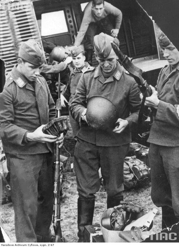Żołnierze Luftwaffe oglądają zdobyczną broń polską Widoczne karabiny Mauser z bagnetami, hełm wz. 31, ładownica i tornister z menażką
