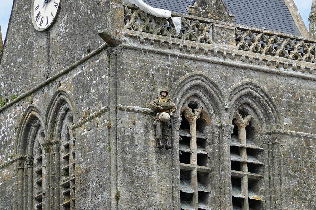 Nietypowe upamiętnienie. Figura alianckiego spadochroniarza znajdująca się na kościele w Sainte-Mère-Église.
