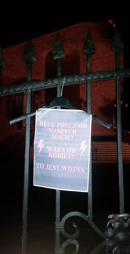 Wieszak i plakat na ogrodzeniu kościoła