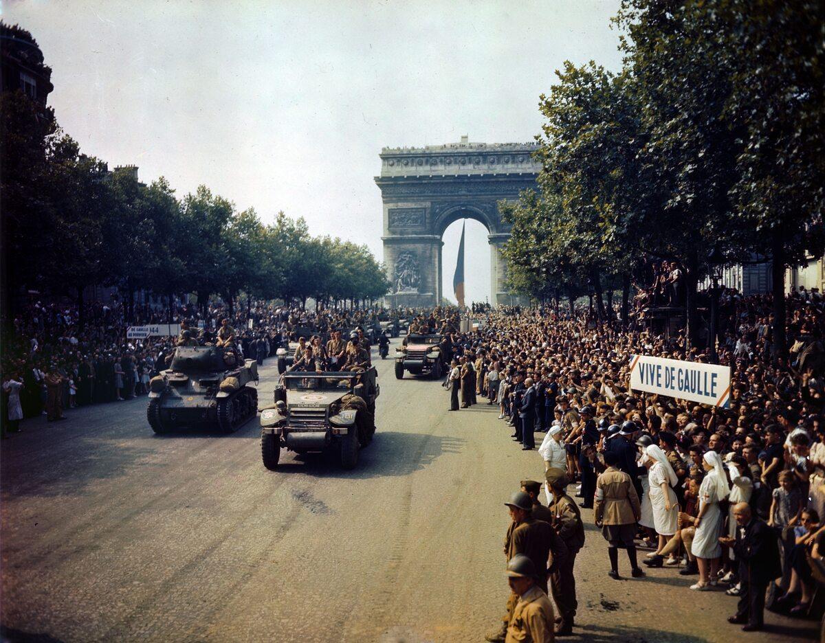 """Parada zwycięstwa na Polach Elizejskich po wyzwoleniu Paryża (26 sierpnia 1944 r.) Napis po prawej głosi """"Niech żyje de Gaulle"""""""