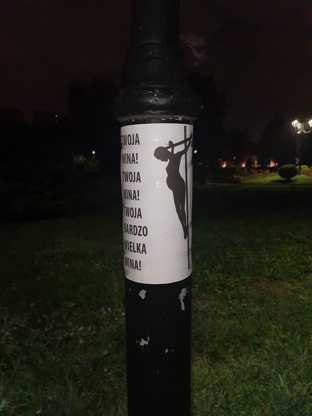 Plakat na latarni koło kościoła
