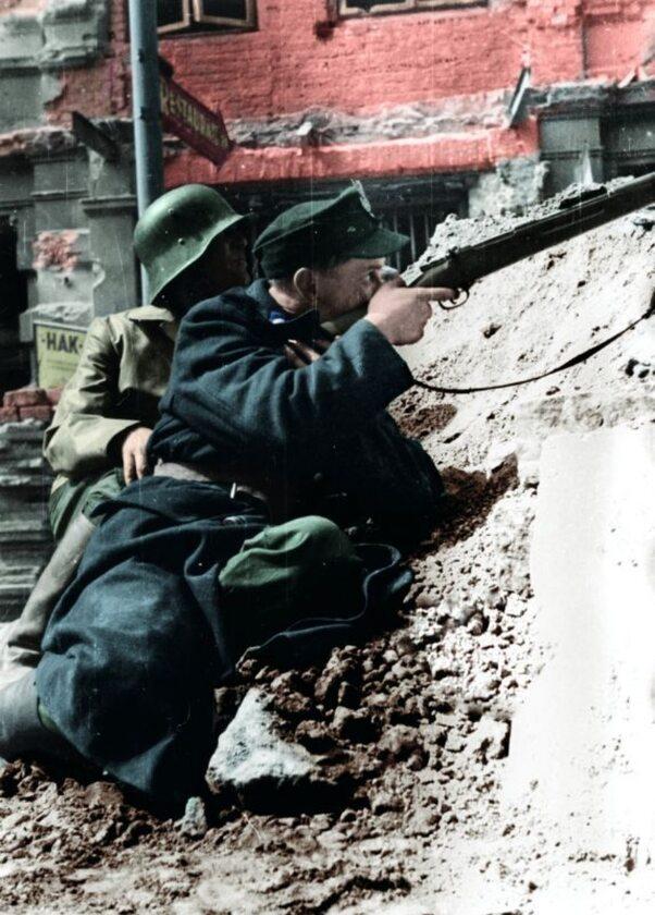 """Powstanie Warszawskie: powstańcy z batalionu """"Kiliński"""" ostrzeliwują budynek PAST-y z poziomu ul. Zielnej (20 sierpnia 1944 r.)"""