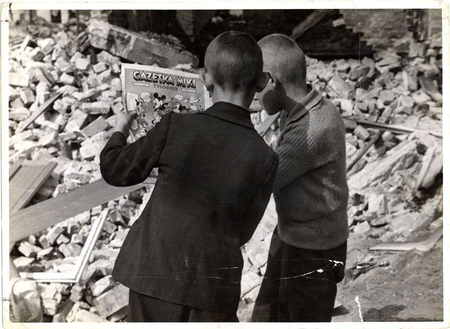 """Dwóch chłopców czyta """"Gazetkę Miki"""" pośród ruin domów. Pismo w formacie tygodnika wydawano w latach 1938-1939"""