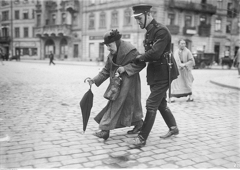 Policjant przeprowadzający staruszkę przez ulicę Krakowskie Przemieście (1925)