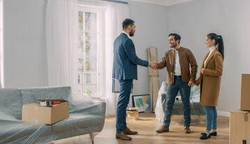 Agent nieruchomości pokazuje parze mieszkanie na sprzedaż