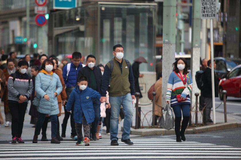 Azjatyccy turyści w maskach na twarzy odwiedzają dzielnicę handlową Ginza w Tokio