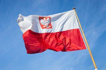 Biało-czerwona flaga z naniesionym na nią godłem