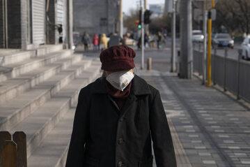 Chiny. Przechodzień w masce ochronnej