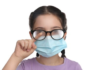 Dziewczynka z okularami w maseczce higienicznej na twarzy, zdjęcie ilustracyjne
