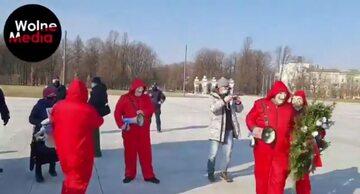 Grupa przebierańców, próbująca złożyć wieniec przed pomnikiem smoleńskim