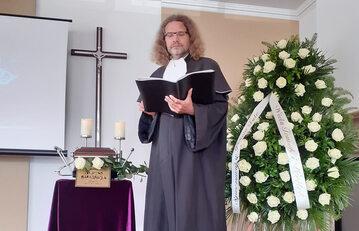 Jacek Borowik, mistrz ceremonii pogrzebowych przy urnie z prochami zmarłego