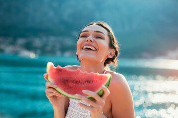 Kobieta jedząca arbuza nad wodą