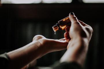 Kobieta nabierająca na dłoń olejek eteryczny