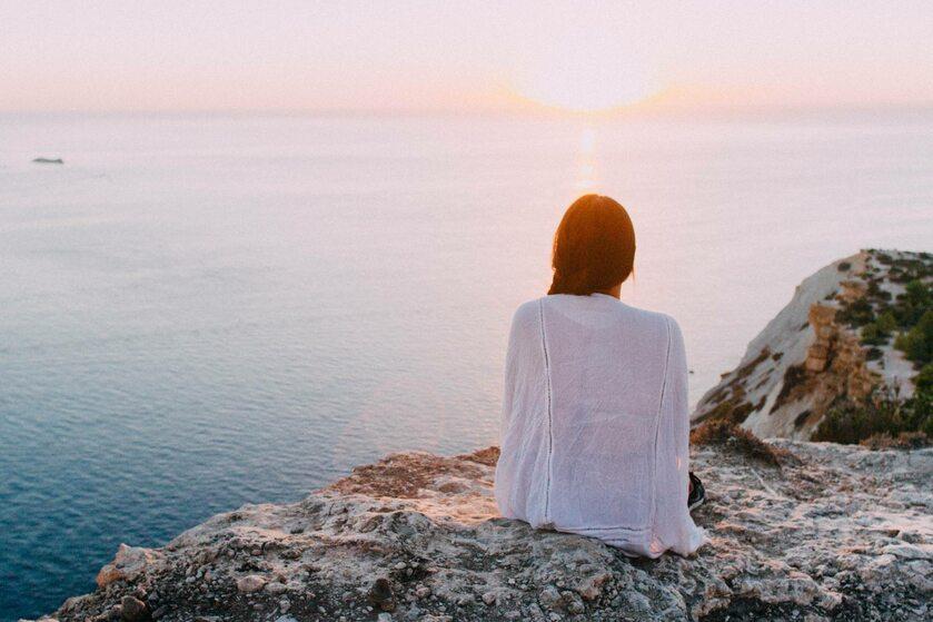 Kobieta patrząca na zachód słońca