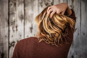 Kobieta przeczesująca placami włosy