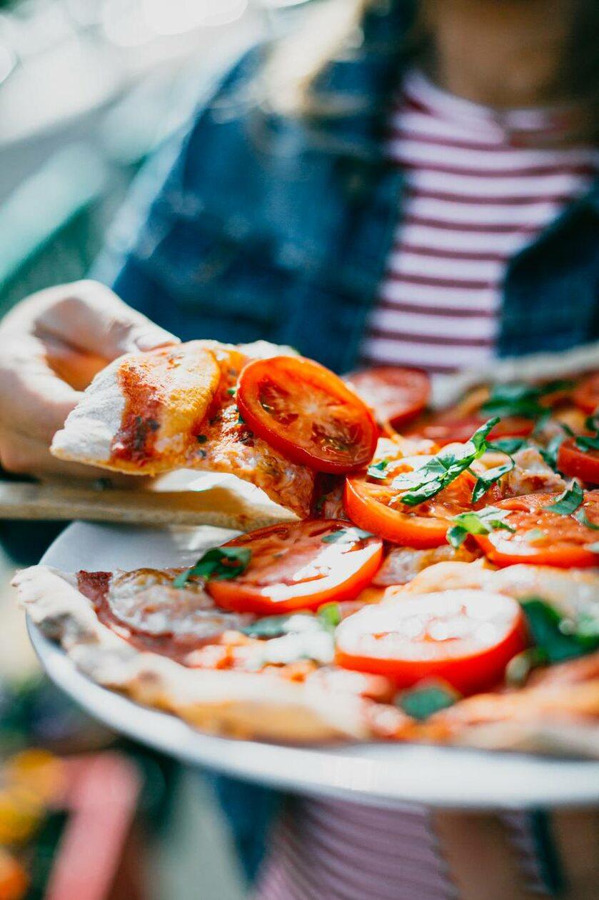 Kobieta sięgająca po kawałek pizzy