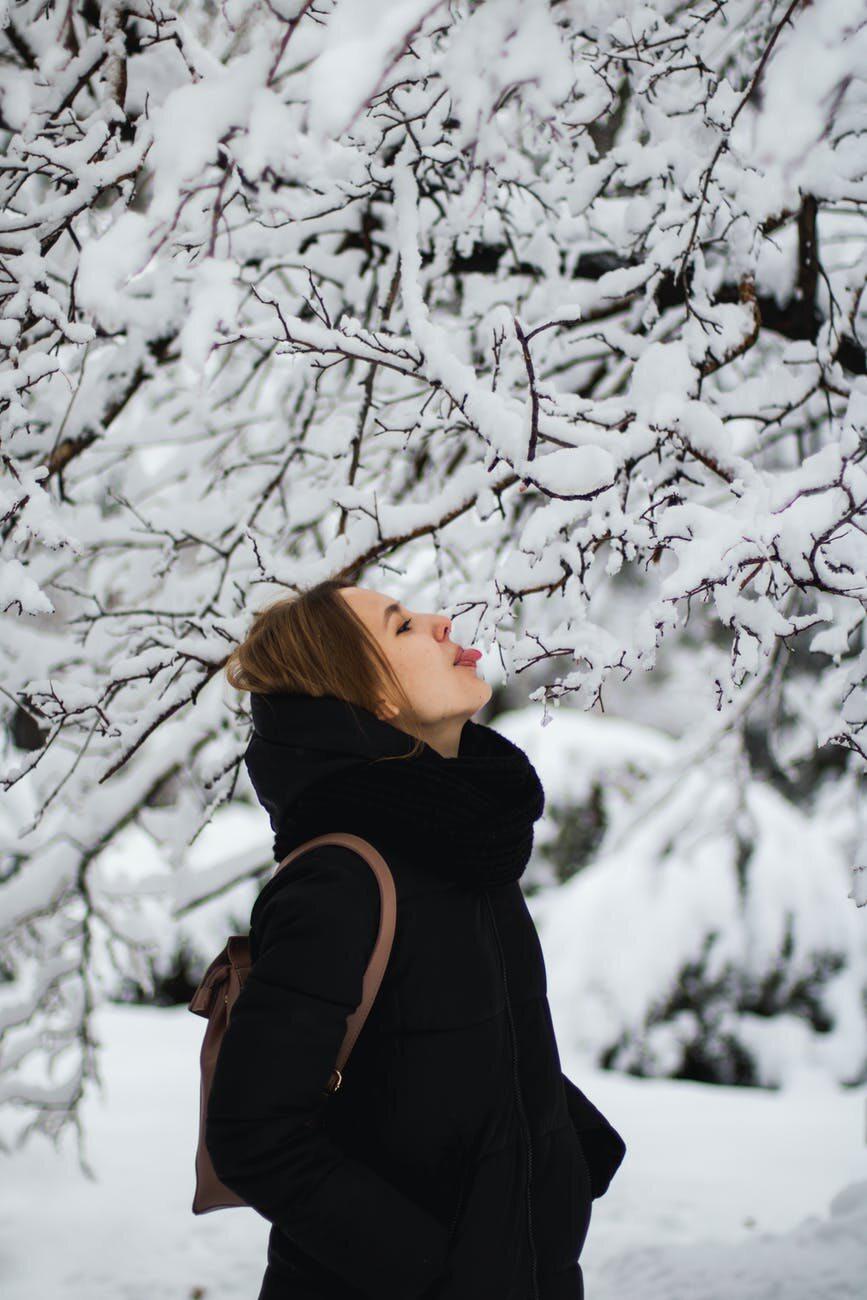 Kobieta usiłująca polizać śnieg