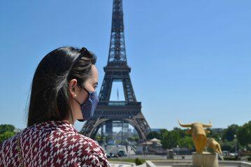 Kobieta w maseczce na tle wieży Eiffle'a