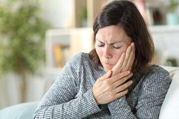 Kobieta z bólem w okolicy policzka