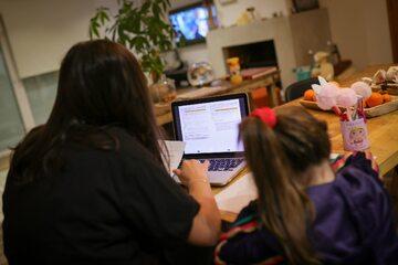 Kobieta z dzieckiem podczas pracy zdalnej w domu