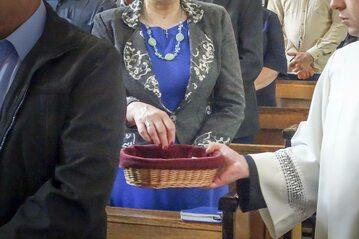 Ksiądz zbiera na tacę podczas mszy