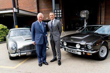 Książę Karol i Daniel Craig na tle Astonów Martinów