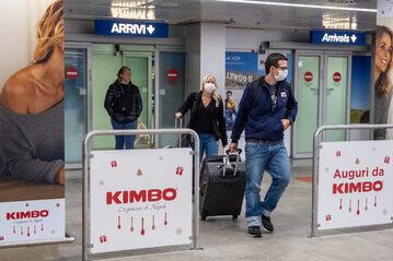 Ludzie w maseczkach na lotnisku w Mediolanie