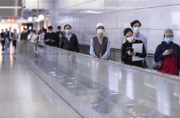 Ludzie w maseczkach na ulicach Hongkongu