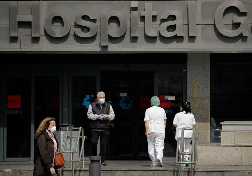 Ludzie w maseczkach przed szpitalem w Madrycie