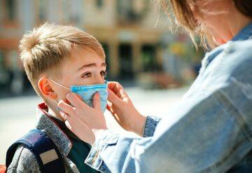 Mama poprawia maseczkę na twarzy dziecka