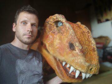 Mateusz Kowalski z głową kostiumu tyranozaura