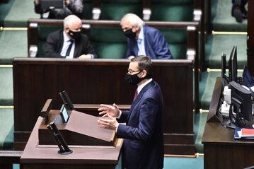 Mateusz Morawiecki przy mównicy w Sejmie, w tle Jarosław Kaczyński i Ryszard Terlecki