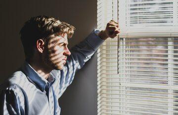 Mężczyzna patrzący przez okno