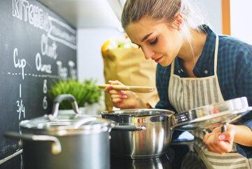 Młoda kobieta w trakcie gotowania