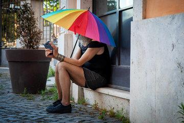 Osoba siedząca pod tęczową parasolką (zdj. ilustracyjne)